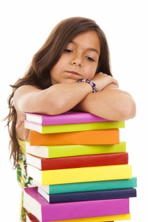 Girl resting her head on a stack of books.