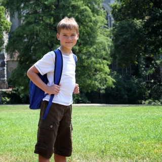 Boy in white shirt with blue backpack.
