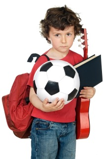 Child in red shirt holding soccer ball, book, and guitar.