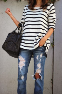 Woman posing in striped shirt and distressed jeans.