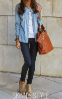 Woman posing in skinny jeans and carrying brown handbag.