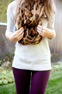 Woman wearing cheetah print scarf and purple jeans.
