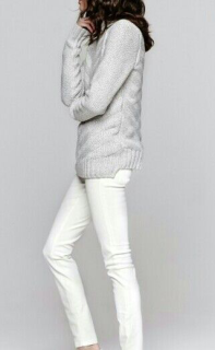 Model posing in gray sweater and white jeans.